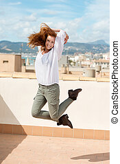 Woman leaping on a flat roof