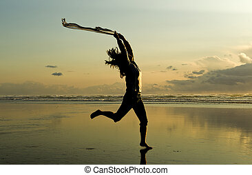 Woman leaps at sunset.