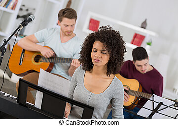 woman learning a music instrument with friends