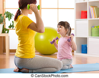 Woman learning child doing fitness exercises with dumbbells