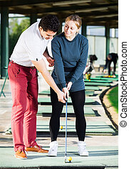 Woman learning to play golf