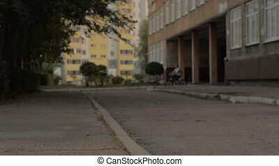 Woman leaves the front door on a bicycle and rides along the asphalt road