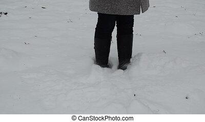 woman leg dig snow - woman legs stand in winter snowdrift...