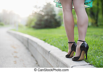 Woman legs and high heels in the park