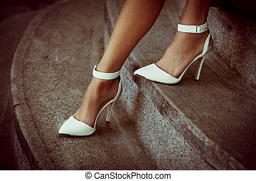 woman legs in elegant white high heel shoes outdoor shot summer day