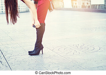 Woman legs in high heels black boots on street background, soft focus and blur, Blank text