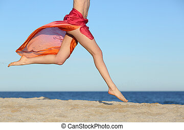 Woman legs jumping on the beach happy with the horizon and ...