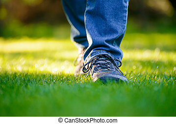 Woman Legs on the Green Grass in Garden