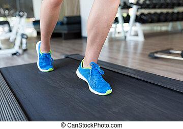 Woman legs on treadmill