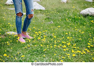 woman legs walk on green grass