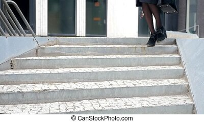 Woman legs walking down the stairs