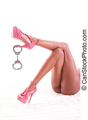 woman legs with handcuffs dangling on shoe heel - legs of...