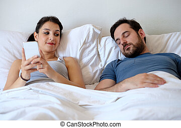 Woman liar having affair and chatting with other man while boyfriend is asleep