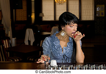 Woman licking a salt chaser at the bar