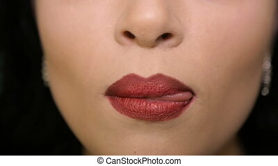 Woman licks his lips with red lipstick - The girl licks his...