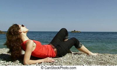 Woman lies near the sea