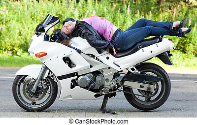 woman lies on a motorcycle
