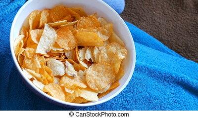 Woman lies on a sofa under a blue blanket and eats potato...