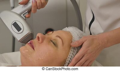 Woman lies on a table in a beauty spa getting a treatment.