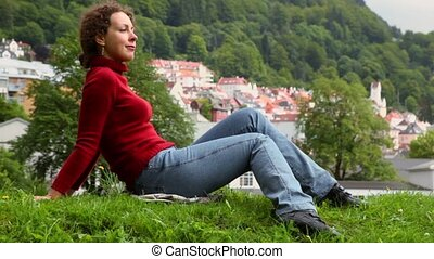 Woman lies on grass at background of Bergen town among trees...
