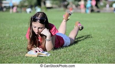 Woman lies on grass reading a book