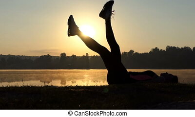 Woman lies on her back and trains her belly at sunset.