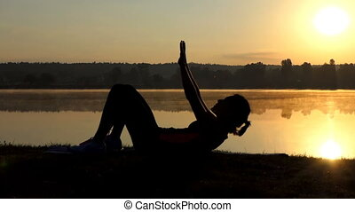 Woman lies on her back and trains her legs at sunset.