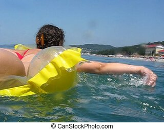 woman lies on inflatable mattress and oars in sea - woman...