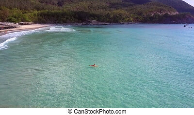 woman lies on surfboard floating in sea against green...