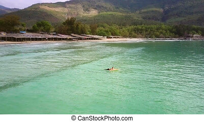 woman lies on surfboard paddles on waves at beach -...