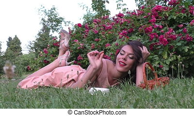 Woman lies under a bush of roses. - Woman lies on the grass...