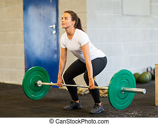 Woman Lifting Barbell - Full length of young woman lifting...