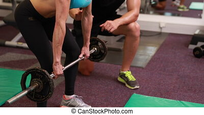 Woman lifting barbell with her trainer at crossfit session...