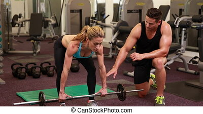 Woman lifting barbell with her trainer