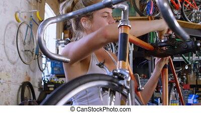 Woman lifting cycle at workshop 4k - Beautiful woman lifting...