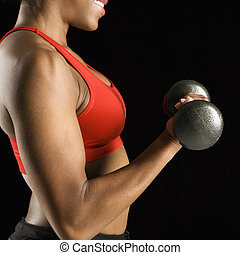 Woman lifting dumbbell. - Torso of African American young...