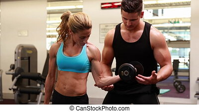 Woman lifting dumbbell with her trainer at crossfit session...