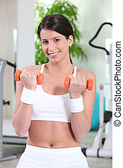 Woman lifting dumbbells at the gym