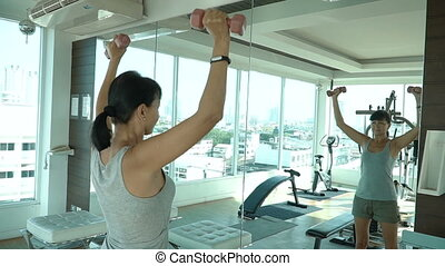 Woman lifting dumbbells in front of the mirror in gym