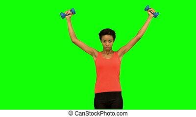 Woman lifting dumbbells on green sc