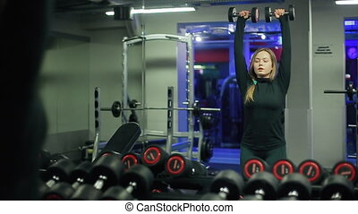 Woman Lifting Dumbbells Weights and Sweating