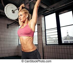 Woman Lifting Weight - Woman doing shoulder press exercise...