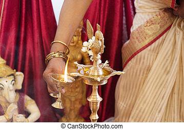Woman lighting up the metal oil lamp
