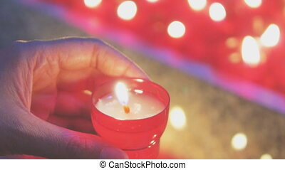 Woman lights a candle near altar in church.
