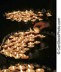 woman lights a candle to pray during mass at Church