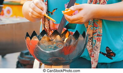 Woman lights a wax candle in the form of a lotus over...