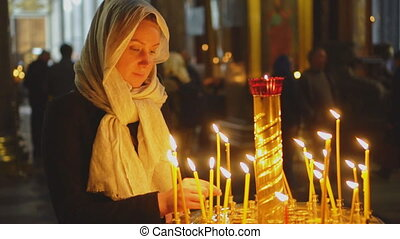 Woman lights the candle in russian orthodox church.