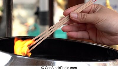 Woman Lights Three Incense Sticks in Open Fire.