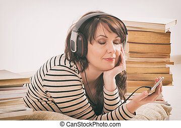 Woman listening an audiobook on smartphone sitting between...