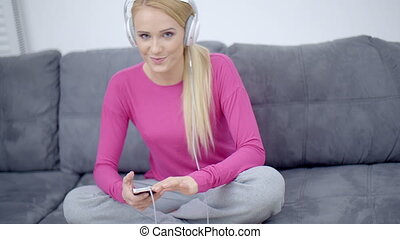 Woman Listening Music From Phone Using Headset